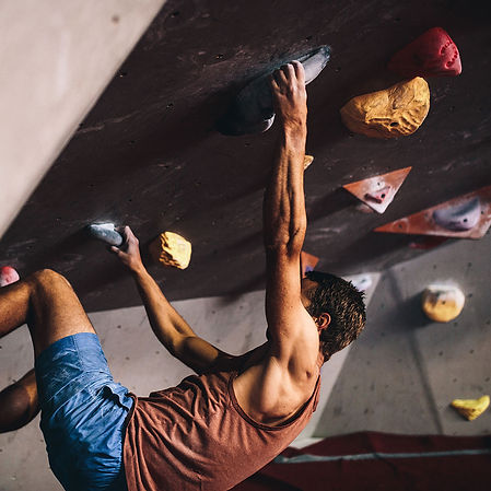 man climbing an indoor climbing wall