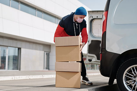 Image of man putting boxes into back a van.