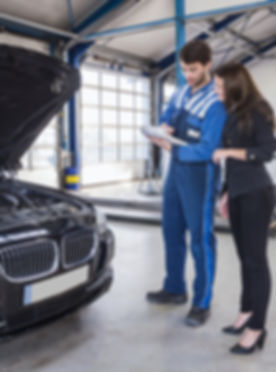 Car mechanic and customer stand next to the serviced car and looking through the checklist.jpg