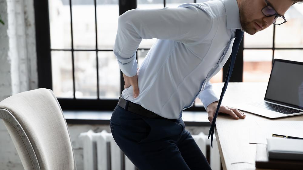Les troubles musqulosquelettiques : personne qui a mal au dos à cause d'une mauvaise posture à son bureau