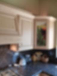 Detalle cocina con cornisa alta en alamo blanco patinado gris encino americanos, campana extractora, alacena derecha, esquinero emplomado con iluminación interna, cubierta en granito natural nariz boleada lambrin de granito detras de parrill horno