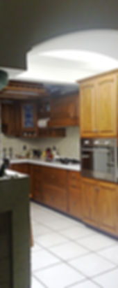 Sobre piso, Torre de horno, cajonera de 3 cjns, 2 cajones caceroleros, cajonera de 4 cjns. Sobre muro, Campana extractora, Alacena esquinera con emplomado iluminado, alacena trastero con cajones en parte inferior. Caja de luz central con riel alrededor. Todo en encino americano selecto color miel