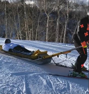 Rebel Wilson getting a tow from the ski patrol