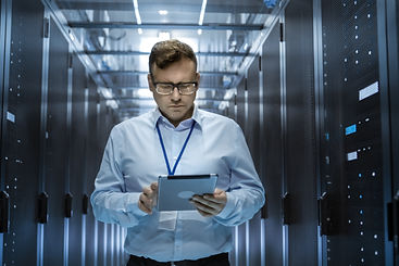 Man in data center holding tablet computer