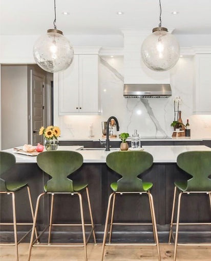 White kitchen with dark green counter stools