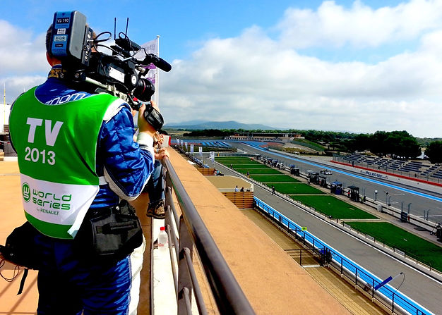 Man stood atop a roof with a film camera on his shoulder looking down on a race track