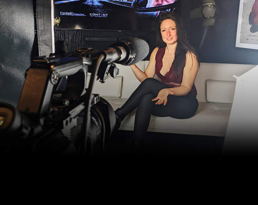 Image of Charlotte Fantelli presenting in front of a camera on a sofa wearing a red top and black leggings with an image of journey to le mans behind her