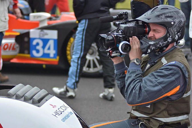 Image of man with camera on shoulder wearing a racing helmet filming a racing car up close
