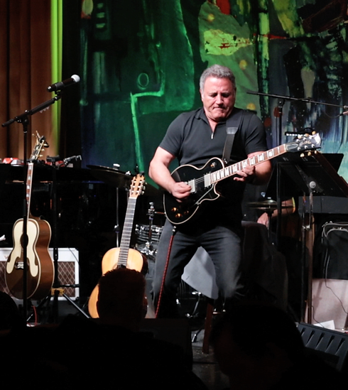 Frank stallone playing guitar on stage