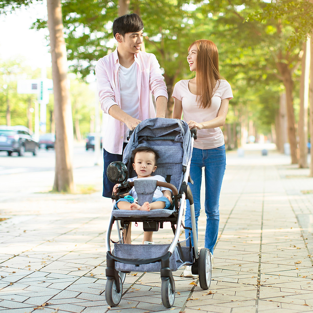 Couple walking baby with stroller