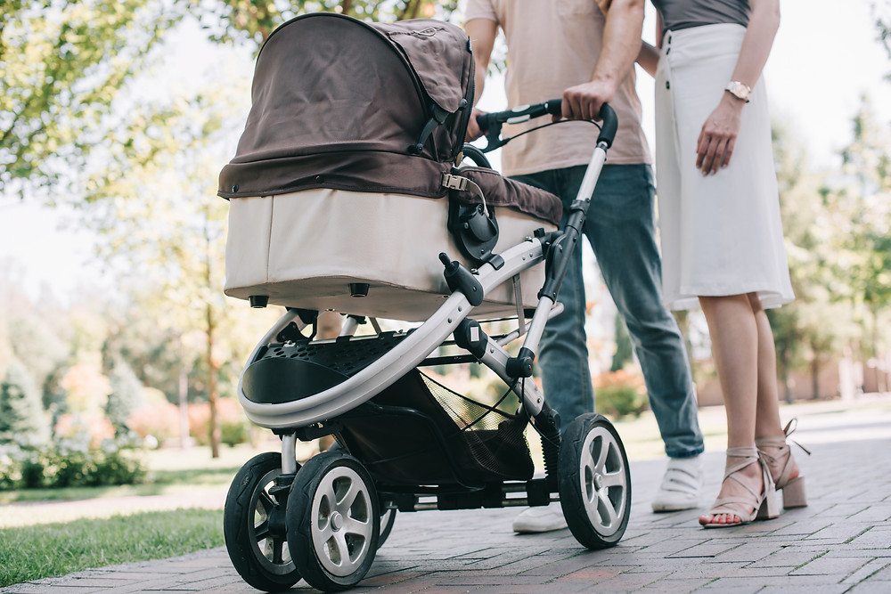 Couple walking baby with a stroller
