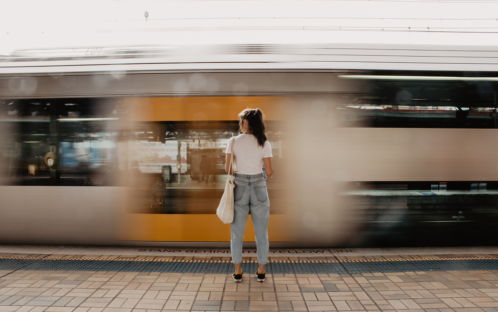 Fast train passing woman on platform