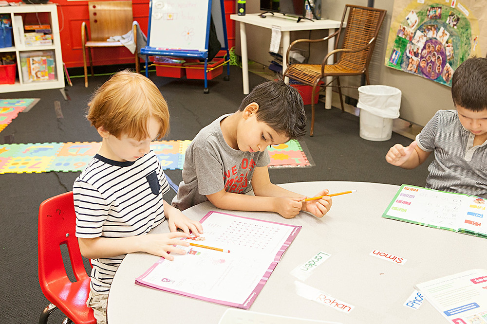 Three young children do schoolwork at a table in a classroom