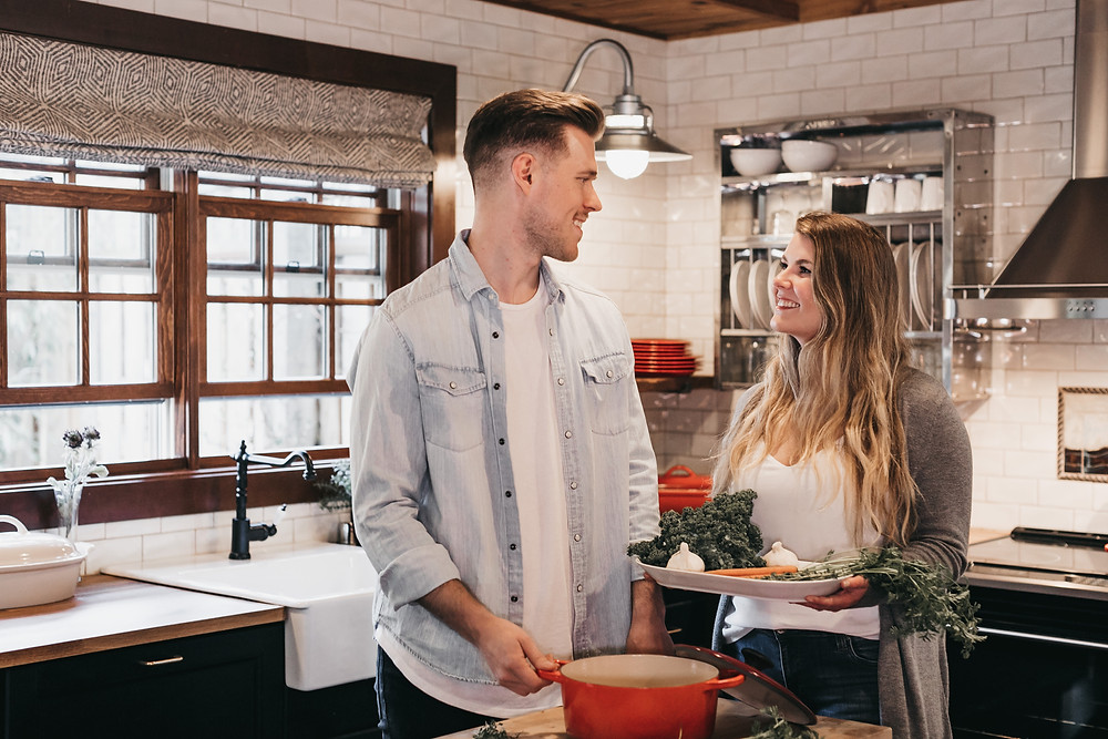 A man and woman talk in a kitchen as the woman holds a plate of veggies