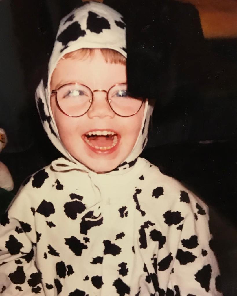 A young Cory smiles widely dressed in an adorable cow costume