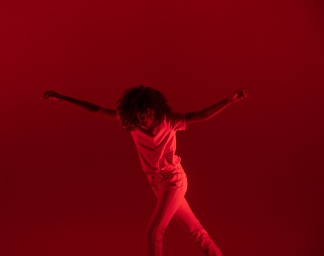 A person dances in deep red light