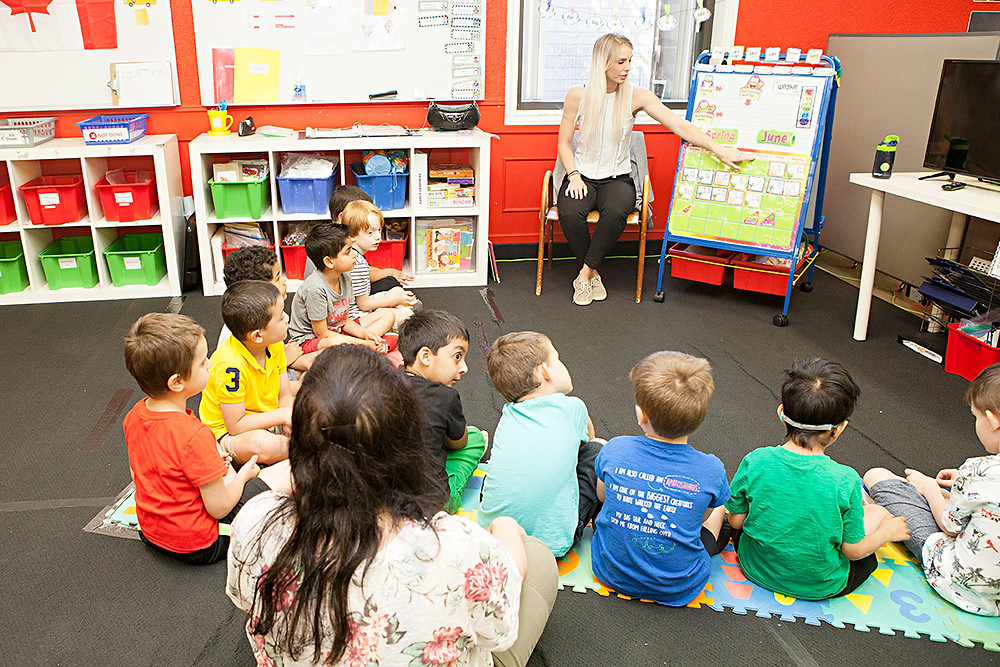 Children sit on the floor facing teacher give a lesson