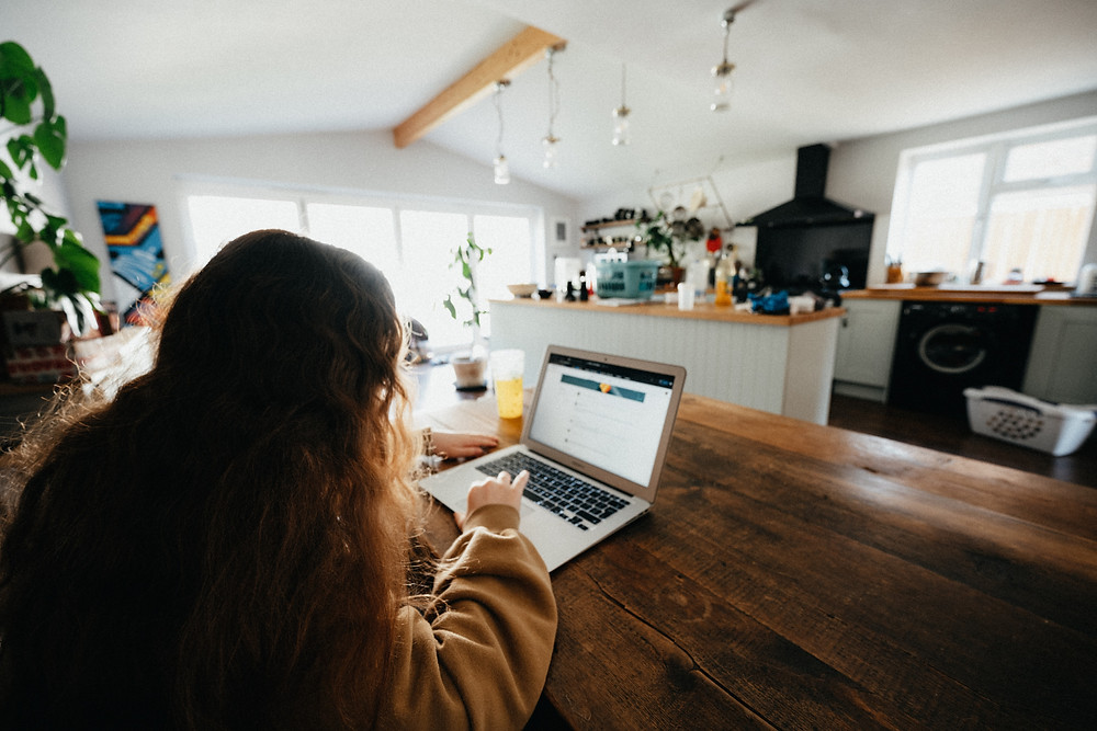 A girl uses her laptop in a kitchen