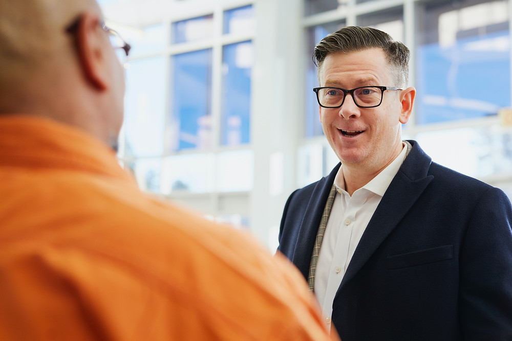 Two men talk, making eye contact