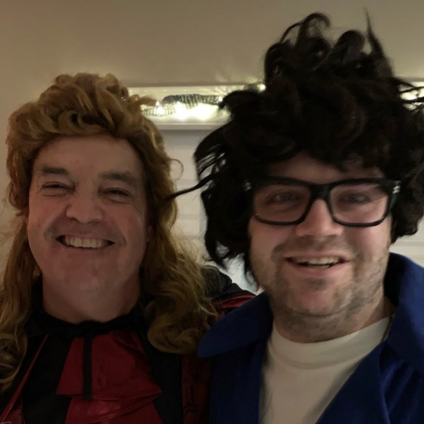 Cory wears a black wig and glasses, standing aside his father who is wearing a blonde mullet wig.