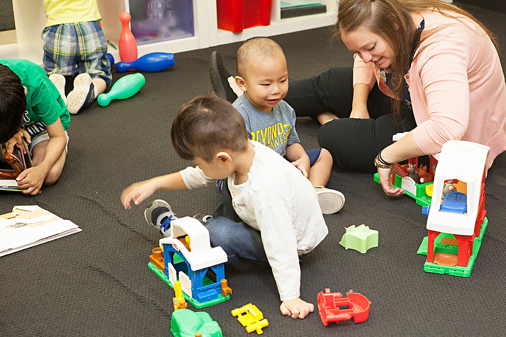 Children and a teacher play with toys on a classroom floor