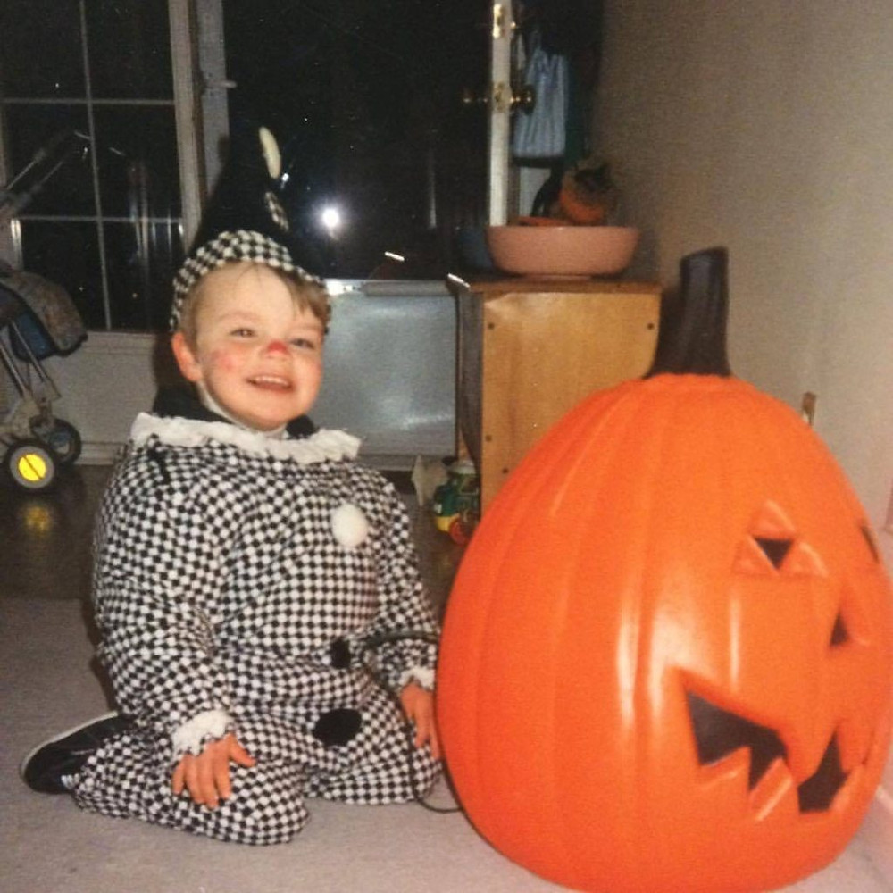 A young child dressed as a wizard sits on the floor next to a plastic Jackolantern that's as big as him