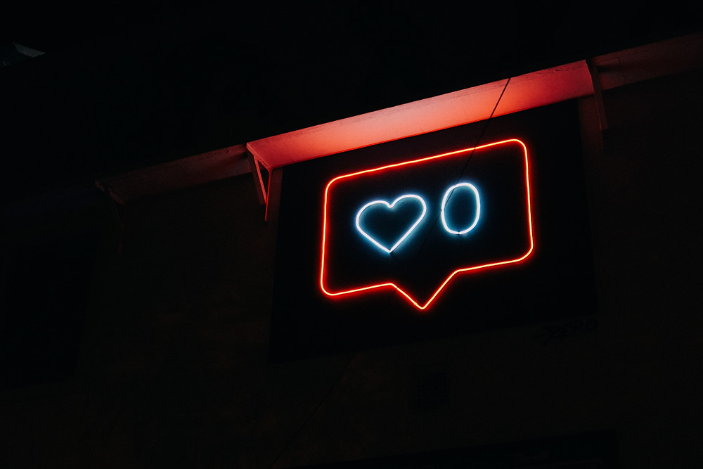 """A neon sign in the shape of a social media """"Like"""" button"""