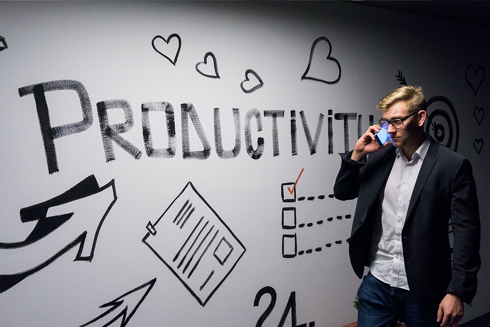 """A man in business casual dress is on the phone. Behind him a wall has a design with the word """"productivity"""""""