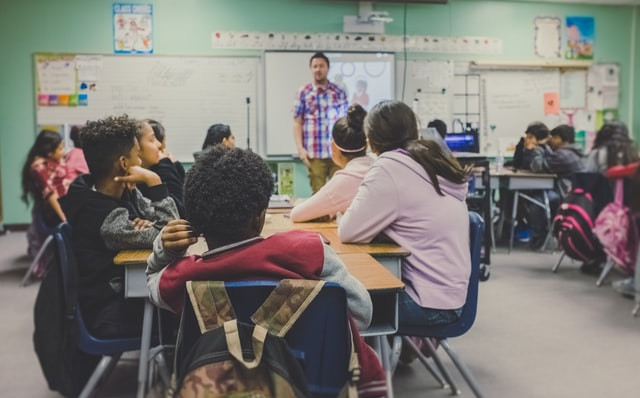 A classroom of 6th graders looks at teacher who is talking