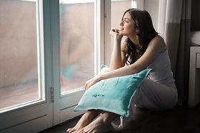 Canva - Woman Holding Teal Pillow.jpg