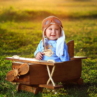 photo-of-baby-sitting-on-wooden-airplane