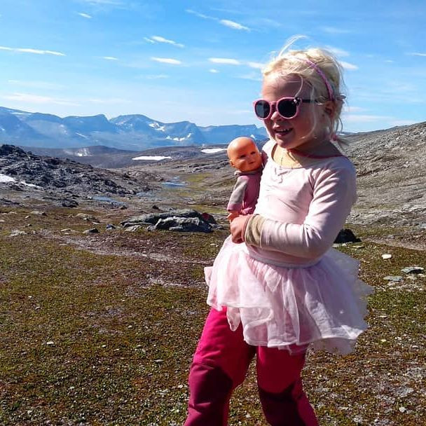 small girl in the mountains wearing a pink tutu