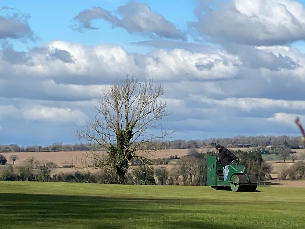 Groundsman rolling a cricket pitch in the countryside