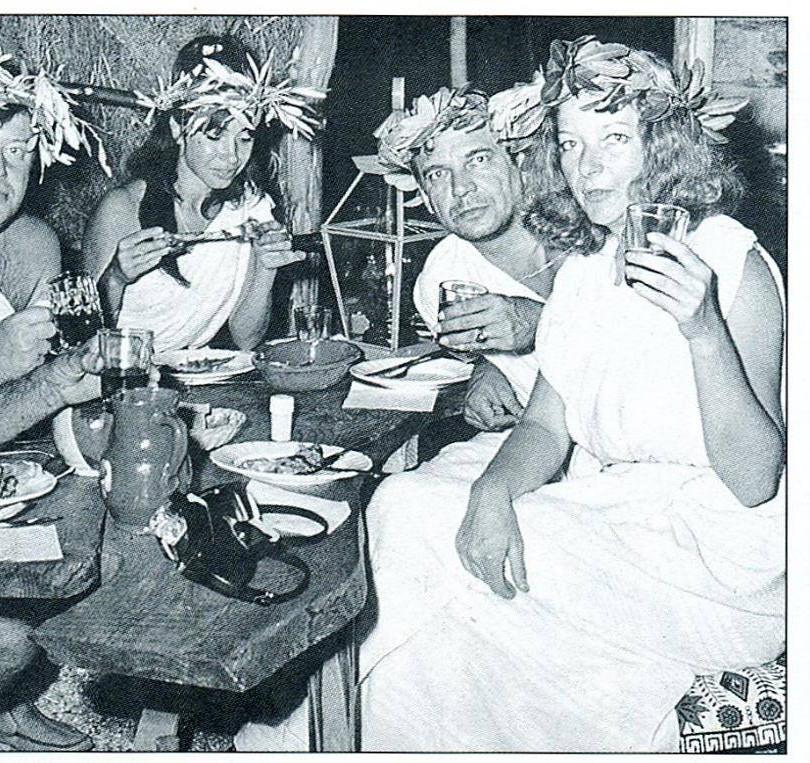 Φιλοξενούμενοι δαφνοστεφανωμένοι γευματίζουν στην καλύβα του Αλφόνς, Μαγνησία στο πέρασμα του χρόνου