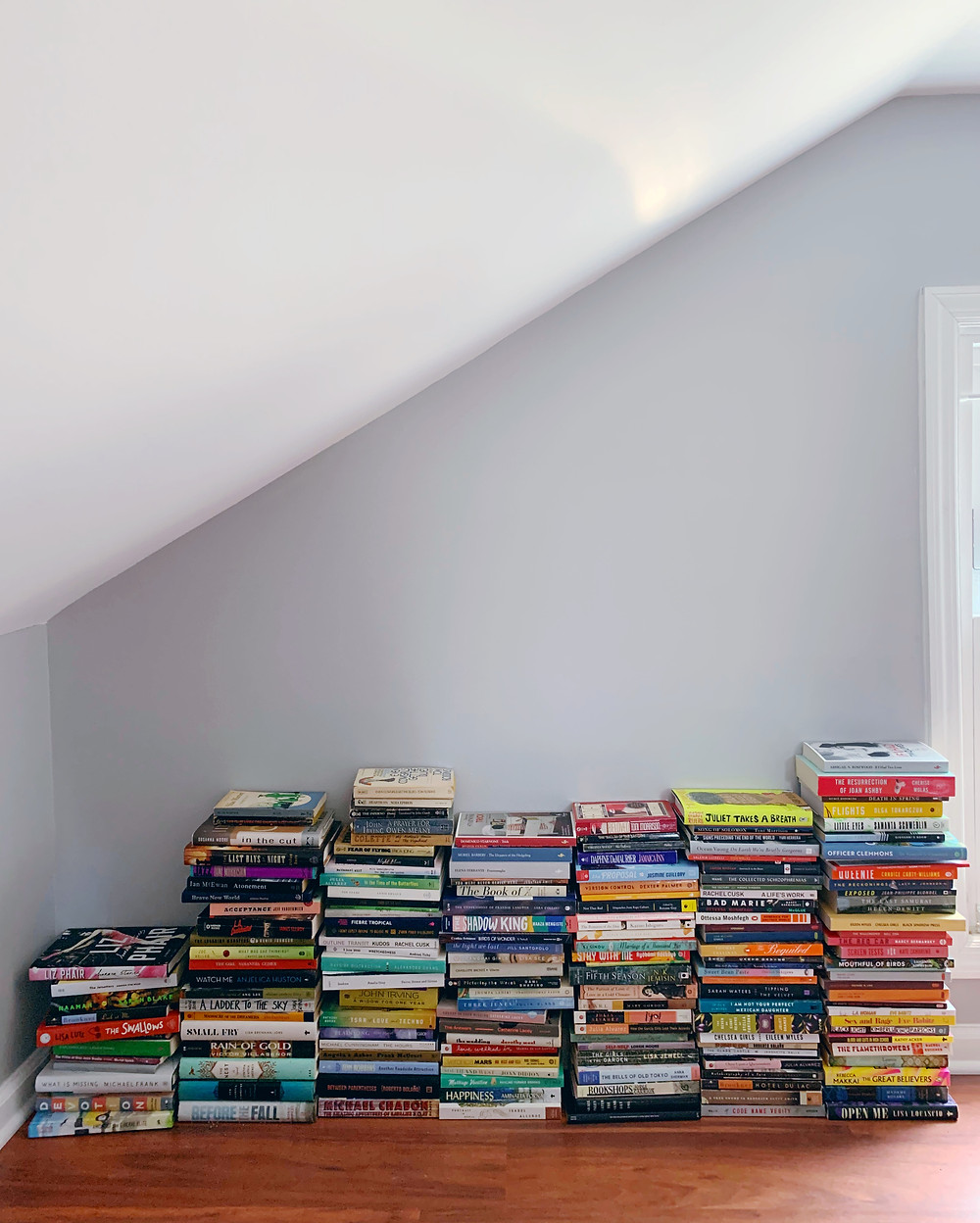 Several piles of books against a wall in an attic