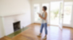 Female Realtor With Digital Tablet Looking Around House