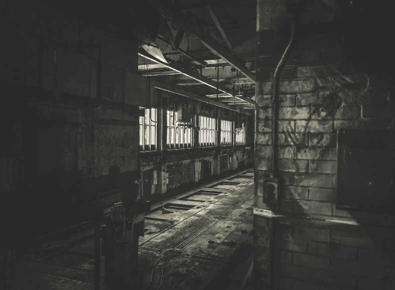 A darkened, black and white image of the interior of the old Pressroom at 35 Blvd of Allies in Pittsburgh
