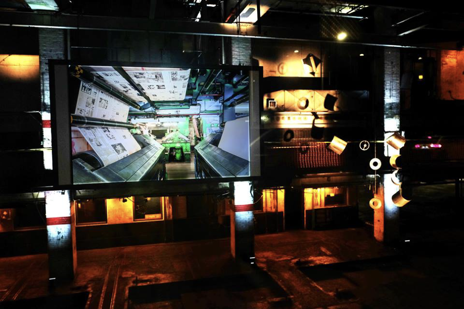 Surrounded by mechanical artifacts lit up with lights, on a screen is projected an image of the last day the printing presses were in use.