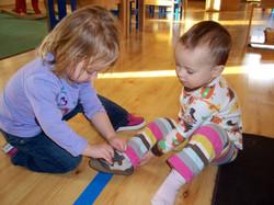 Older toddler helping a friend