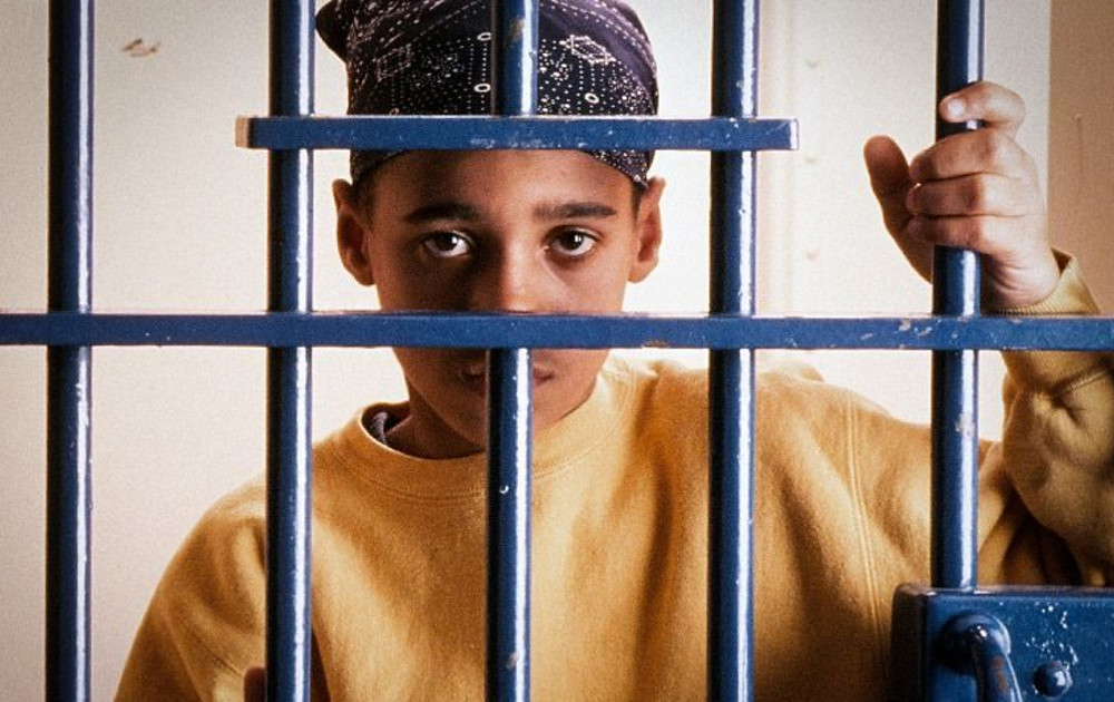 A young boy staring out from a jail cell. (Image Source: gcdd.org)
