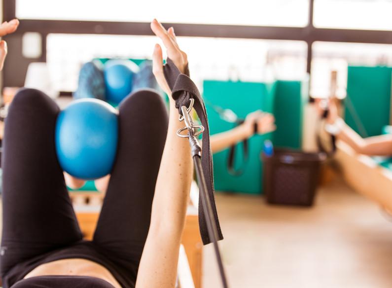 Woman training pilates on reformer appar