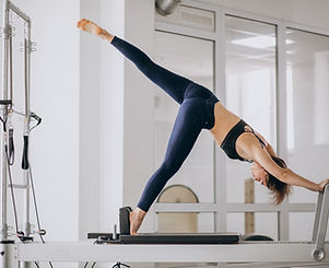 Woman practising pilates in a pilates re