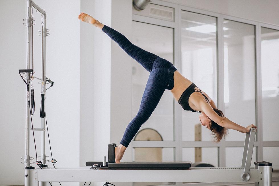 Woman practising pilates in a pilates reformer.jpg