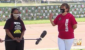 Image of Lowry Manders, a white woman, and Denita Jones, a Black woman, being interviewed with a microphone in front of them
