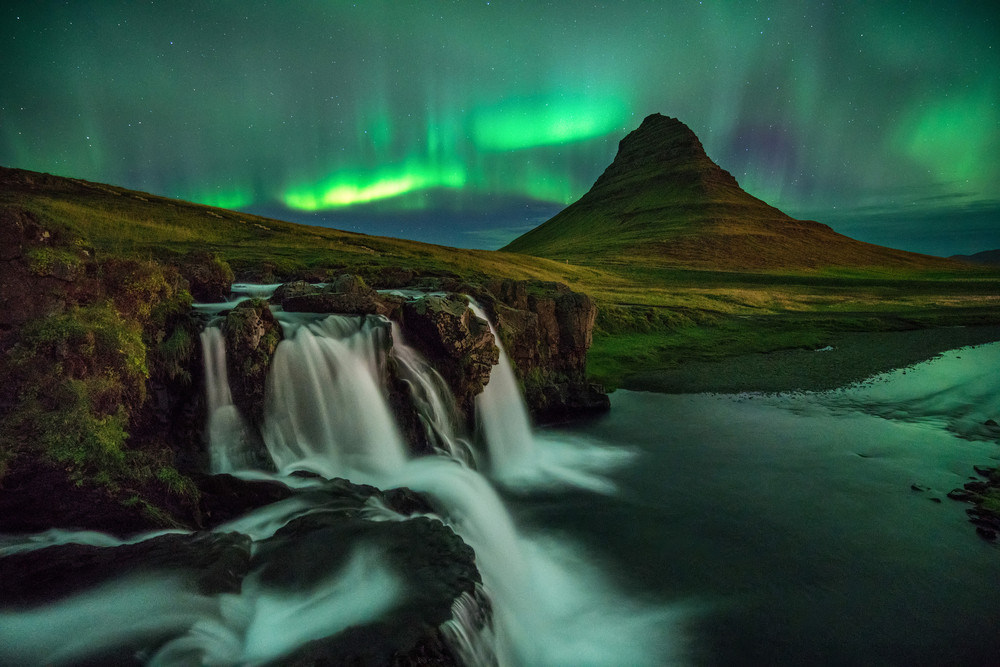Impressive Iceland photography of a waterfall, mountain and green Aurora at night. dark greens and glowing white of the water.