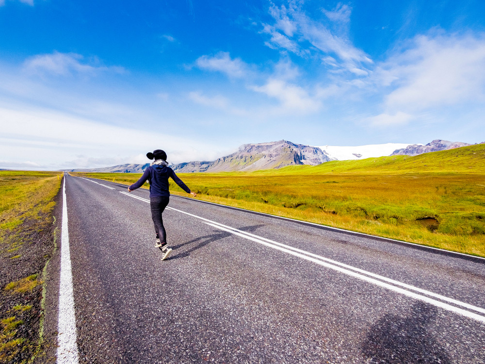 Female traveller skips along a scenic open road. Iceland Ring Road