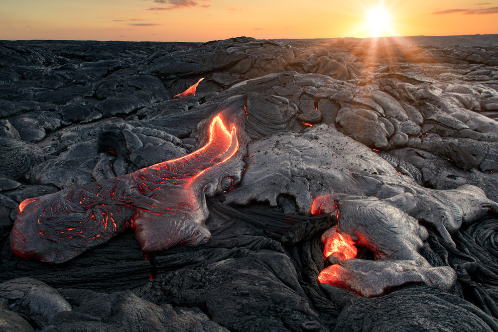 Black cooled lava flow with glowing magma under sunset sky. Volcanoes of Iceland.