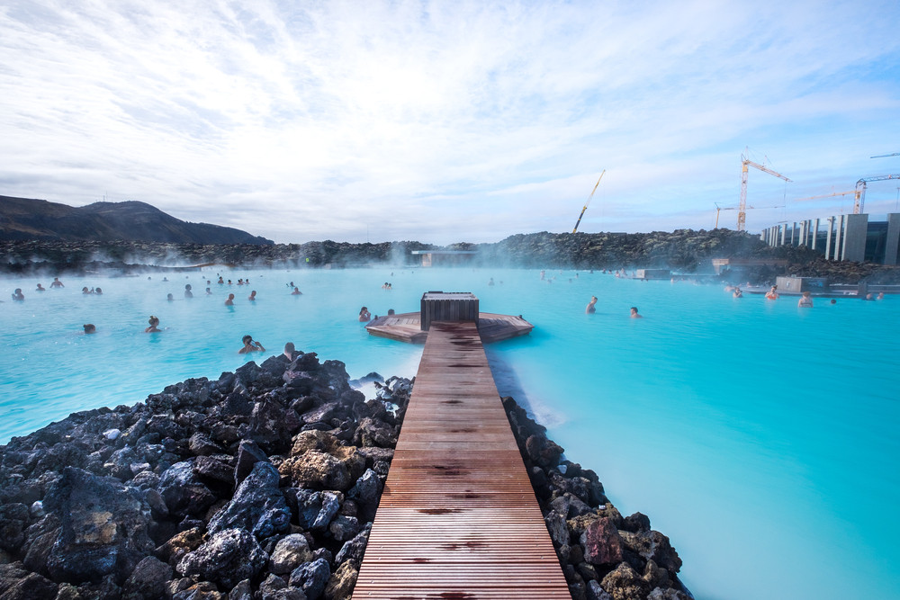 A large lake surrounded by black volcanic rock. Beautiful turquoise waters and a wooden walkway. Iceland's hot springs.