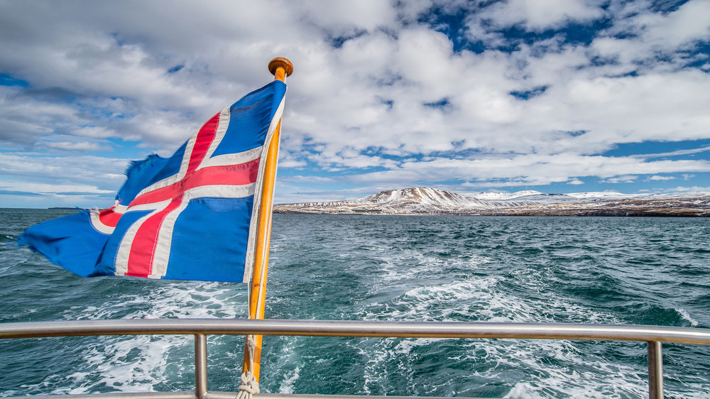 Iceland national flag flying on the back of a boat heading away from a winter coastline.