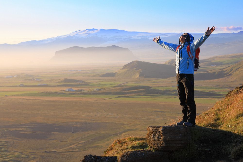 A hiker stands arms raised looking out across beautiful mountains and plains. Hiking in Iceland.